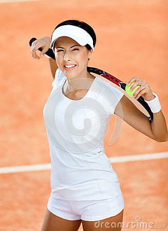 Sportive woman keeps tennis racket on shoulders