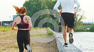 Sportiver Paarlauf entlang einer konkreten Leiste entlang dem Damm in Richtung zum grünen Wald stock video