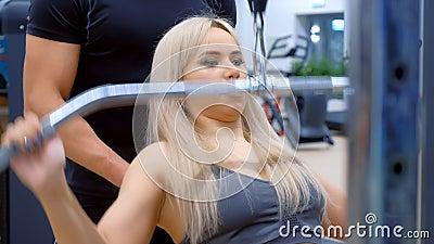 Sportowa kobieta z trenerem wykonująca ćwiczenia na mięśniach uzbrojenia na maszynie szkoleniowej zbiory