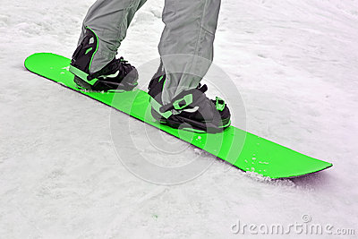 Sportsman with green snowboard on white snow, seasonal sport,