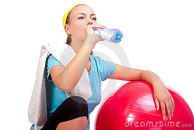 Sportswoman drinking water after training