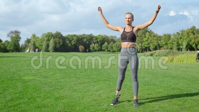 Sportswoman warming before workout in park. Woman warming arms in green area. Sportswoman with artificial limb warming before workout in summer park. Fitness stock video