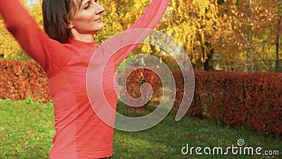 Sportvrouw danst op choreografieles in het herfstpark Danser vrouw traint op danslessen in de buitenlucht in een kleurrijk park stock footage