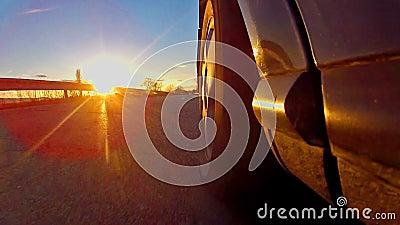 sportwagenras met zonsondergangstralen die op band glanzen stock videobeelden