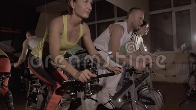 Sporty fitness group of three training on stationary bikes doing exercise synchronously. In studio with artificial light. Slow motion
