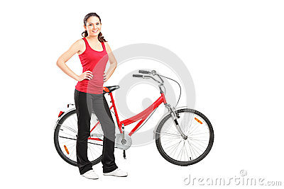 Sporty girl posing next to a bike