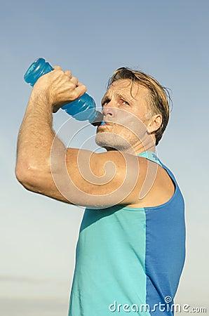 Sporty man drinking from bottle