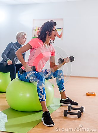 Free Sporty Slim Women Taking Part In Gym Fitness Class Exercising Sitting On Physioballs Doing Alternated Biceps Curl With Stock Photos - 107670513