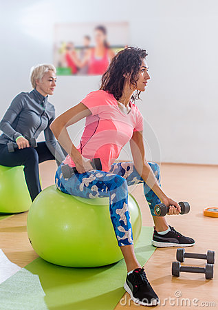 Free Sporty Slim Women Taking Part In Gym Fitness Class Exercising Sitting On Physioballs Doing Alternated Biceps Curl With Stock Photos - 86551593