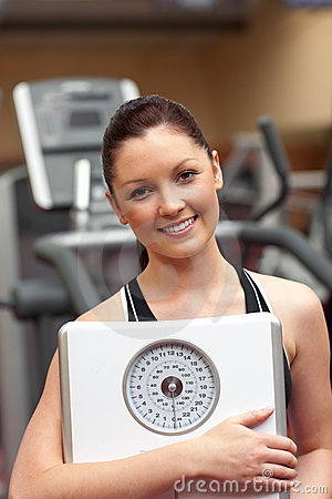 Sporty woman holding a scale