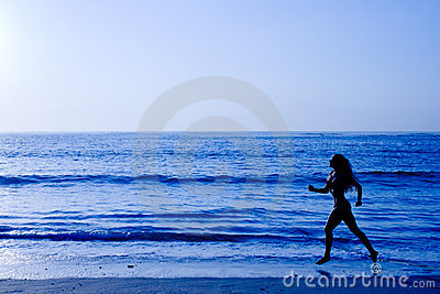 Sporty woman running along beach