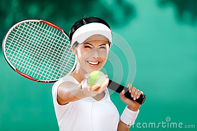 Sporty woman serves tennis ball