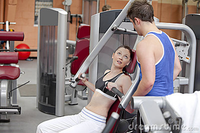 Sporty woman sitting on a shoulder press talking