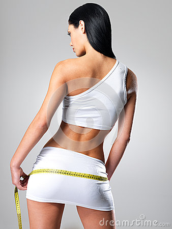 Sporty woman with slim body measuring hips