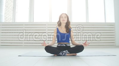 sporty young woman practicing yoga sitting in half lotus