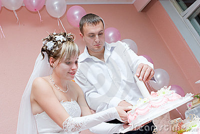 Sposa e sposo con una torta di cerimonia nuziale