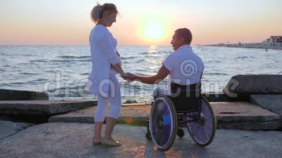 Spouse in wheelchair holds arm woman with big belly, happy couple waiting for baby, disabled person keeps hand of wife Stock Photo