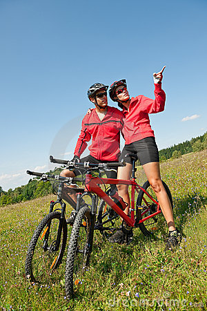 Spring bike - Young sportive couple in meadow