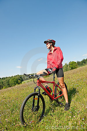 Spring bike - Young sportive woman in meadow