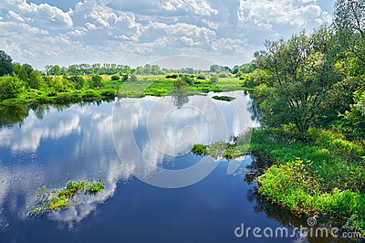 Spring landscape with river and clouds on the blue