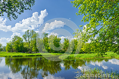 Spring landscape with river and clouds on blue sky