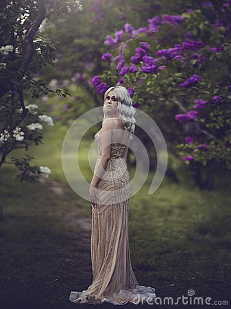 Free Spring Style. Beautiful Sensual Girl Blonde In Spring. Blossoming Spring Garden. Young Girl In A Gold Elegant Dress Royalty Free Stock Photos - 117787238