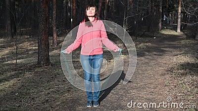 Springendes Seil der Eignungsfrau Frau r?ttelt im sonniger Tageslicht in den Herbstb?umen Hintergrund, das M?dchen, das drau?en a stock video