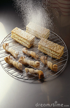 Sprinkling  icing sugar over the pastries