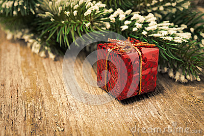 Spruce branch with snow, red gift box on vintage wood