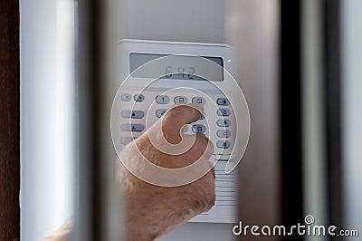 Spying a man arming a burglar alarm system