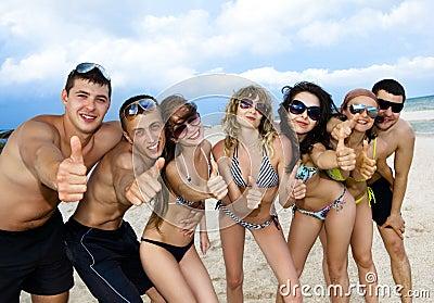 Squadra di amici che hanno divertimento alla spiaggia