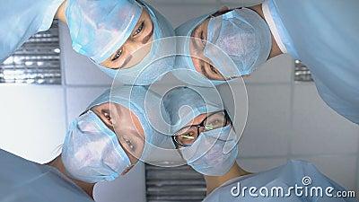 Squadra di chirurgo sorridente, paziente che si sveglia dopo un'anestesia operatoria archivi video