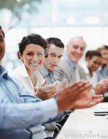 Squadra positiva di affari che applaude ad un congresso