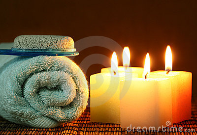 Square candle with blue towel and pumice stone