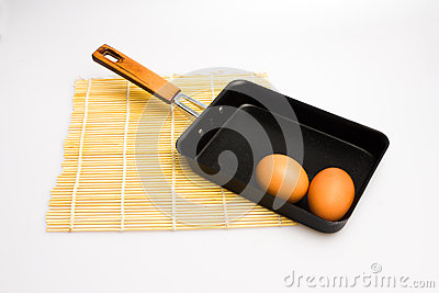 Square japanese frying pan with eggs and sushi mat