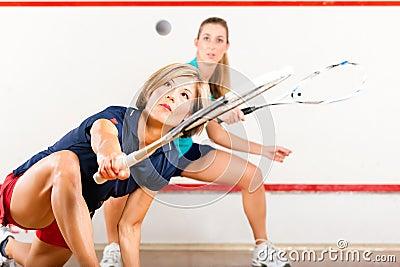 Squashsport - kvinnor som leker på idrottshalldomstolen