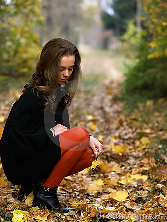 Squatting beauty girl in fall outdoor