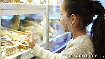 Stäng sig upp skott av en nätt liten flicka som posinting på efterrätterna på bagerit lager videofilmer
