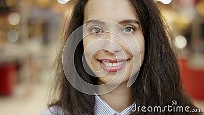 Stäng upp porträttbilden av en vacker ung kvinna som glatt ser positivt och glädjande ut i stormarknaden med stock video