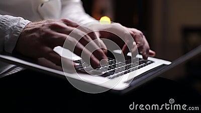 Stängning av manliga händer arbetar med maskinskrivning med hjälp av en bärbar dator på ett mörkt hemmakontor, på knän stock video