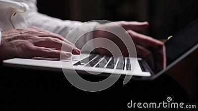 Stängning av manliga kaukasiska händer som skriver på tangentbord på bärbara datorer i mörkt rum, bärbar dator på knä arkivfilmer