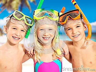 Stående av de lyckliga barnen som tycker om på stranden