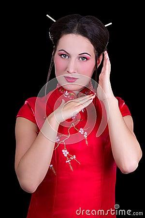 Stående av den härliga kvinnan i den röda japanska klänningen som isoleras på b