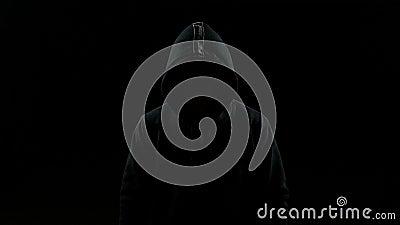Stående av den osynliga mannen med en huv som inomhus nickar hans huvud arkivfilmer