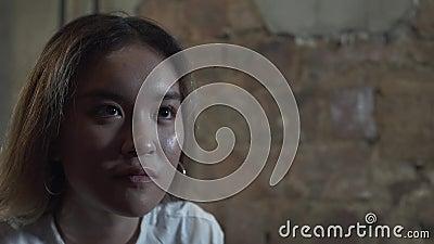 Stående av den unga härliga flickan som fokuseras på att spela videospel på lekstation med hennes vän som kyler i afton stock video