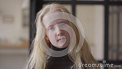 Stående av en albinoflicka med gråa ögon som ser le för kamera Ovanligt utseende Carefree barndom Framsida av arkivfilmer
