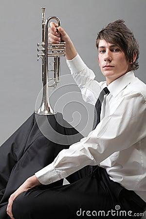 Stående av en ung man och hans trumpet