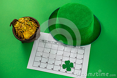 St. Patricks Day leprechaun hat with shamrock, calendar and pot with chocolate gold coins Stock Photo