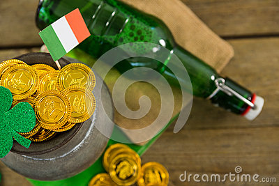 St. Patricks Day shamrock, flag, beer bottle and pot filled with chocolate gold coins Stock Photo