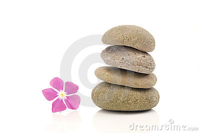 Stack of balanced pebbles with pink flower